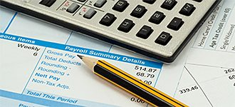 pen and calculator on payroll report